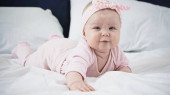 kojenecká holčička ležící doma na posteli