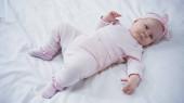 vysoký úhel pohledu na holčičku v čelence s lukem ležící na posteli