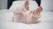ostříhaný pohled na bosé dítě ležící na posteli