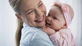 veselá matka drží v náručí šťastný dítě dcera