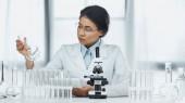 Afrikanisch-amerikanischer Wissenschaftler in Brille mit Fläschchen in der Nähe des Mikroskops