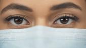 zblízka africký americký lékař v lékařské masce při pohledu na kameru