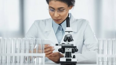 African american scientist looking and smartphone near microscope in lab stock vector