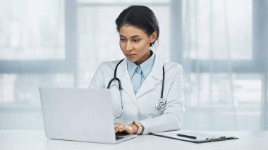 African american doctor using laptop near clipboard on desk stock vector