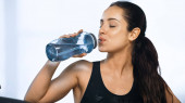 young sportive woman holding sports bottle and drinking water in gym
