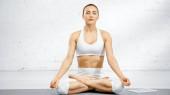 Žena sedící v lotosu pózuje poblíž digitálního tabletu na podložce jógy