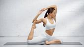 Sedící žena v józe pózuje na podložce