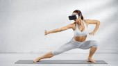 Barfüßige Frau mit Kopfhörer steht auf Yogamatte