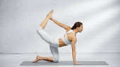 Boční pohled na ženu cvičit jógu pózu v blízkosti bílé zdi doma