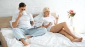 tetovált férfi olvas utazási újság és kávézás közelében nő használ okostelefon az ágyban