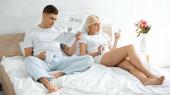 tetovált férfi olvasás utazási újság közelében nő gazdaság csésze kávé és okostelefon az ágyban