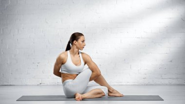 Fit woman doing half lord of fishes pose on yoga mat