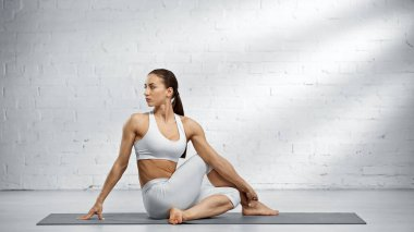 Sportswoman sitting in half lord of fishes pose