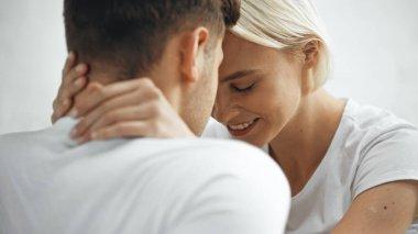 Sarışın mutlu kadın bulanık önplanda erkek arkadaşına sarılıyor.