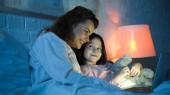Mosolygó gyermek játékmackó nézi anya használ laptop az ágyban