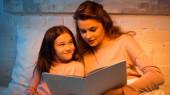Pozitivní dítě při pohledu na matku s knihou v ložnici během večera