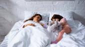 Anya és a gyerek puha játékkal lefekszenek egymással az ágyban