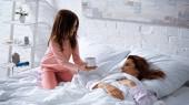 Usmívající se dívka drží šálek kávy v blízkosti matky na posteli