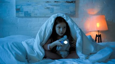 Child with flashlight and teddy bear sitting under blanket on bed during night stock vector