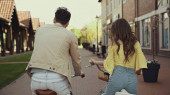 back view of man and woman riding bicycles on street