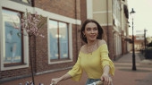 happy young woman in yellow blouse looking away while riding on bicycle outside
