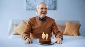 glücklicher älterer Mann feiert Geburtstag vor Kuchen mit brennenden Kerzen im Wohnzimmer im Wohnzimmer