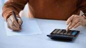 ořezaný pohled na muže starší muž pomocí kalkulačky a psaní perem na šedém pozadí