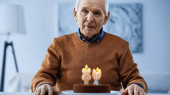 osamělý starší muž sedí před narozeninovým dortem se svíčkami a dívá se do kamery v obývacím pokoji