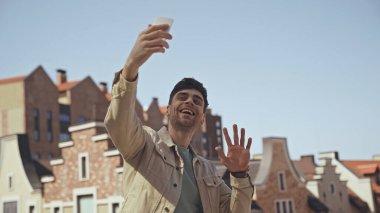 Mutlu adam akıllı telefondan video görüşmesi yaparken el sallıyor.
