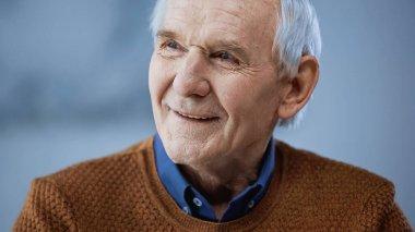 Portrait of cheerful elderly man looking away on grey background stock vector