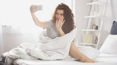 Positive young woman waving hand and having video chat on smartphone in bedroom stock vector