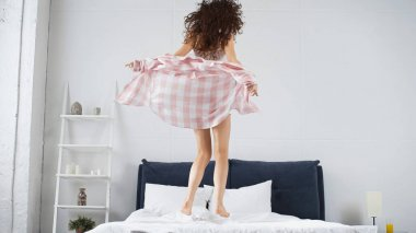 Full length of curly young woman jumping on bed stock vector