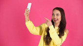 smiling young adult woman taking selfie and pointing with finger at cellphone isolated on pink