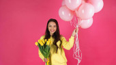 smiling young adult woman holding bouquet of tulips and balloons isolated on pink