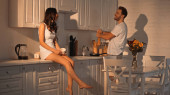 brunette woman sitting on kitchen cabinet with cup near positive boyfriend with pepper shaker