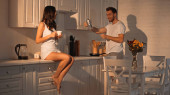 brunette woman sitting on kitchen cabinet with cup near boyfriend with coffee pot