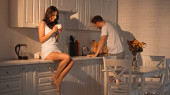 happy woman sitting on kitchen cabinet with cup near boyfriend