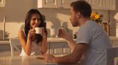 joyful woman holding cup of coffee and smiling near blurred boyfriend
