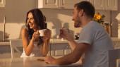 glückliche junge Frau hält Tasse in der Hand und lächelt neben verschwommenem Freund