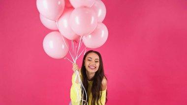 Joyful young adult woman in yellow sweatshirt holding balloons isolated on pink stock vector