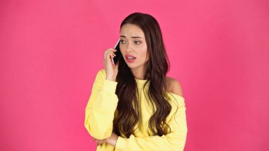 Worried young adult woman speaking on cellphone isolated on pink stock vector