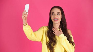 Smiling young adult woman taking selfie on cellphone and holding hand on chest isolated on pink stock vector
