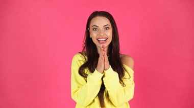 Positive young adult woman in yellow blouse looking at camera with praying hands isolated on pink stock vector
