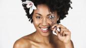 Usmívající se africká americká žena s květinou ve vlasech pomocí řasy curler izolované na šedé