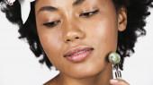 Zblízka pohled na africké americké ženy s orchidejí ve vlasech pomocí nefritový válec izolované na šedé