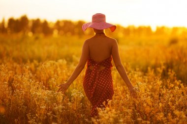 Woman in a hat walking through fields of flowers