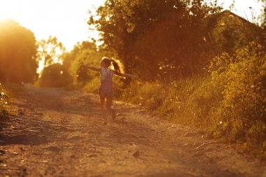 Happy little girl running along a country road