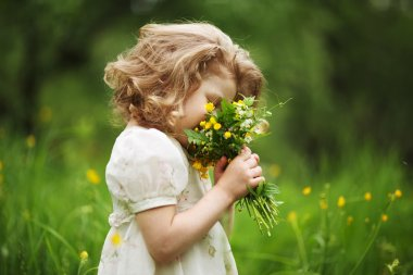 Little girl smelling a bouquet of flowers