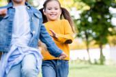 Veselý dívka běží v blízkosti přítele na rozmazané popředí v parku