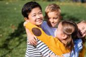 Asijské chlapec při pohledu na kameru při objímání usmívající se přátelé venku